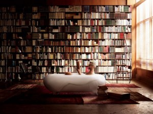 A-cozy-bathroom-with-beautiful-white-bath-tub-red-floor-mat-a-chair-and-a-book-shelf-covered-the-wall